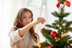 Mujer joven feliz que adorna el árbol de navidad Fotografía de archivo libre de regalías