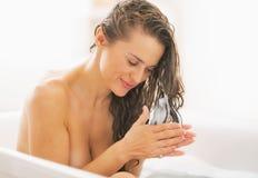 Mujer joven feliz que aplica el acondicionador de pelo en bañera imagenes de archivo