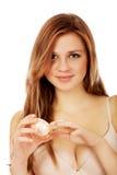 Mujer joven feliz que aplica la crema hidratante poner crema Foto de archivo libre de regalías