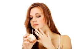 Mujer joven feliz que aplica la crema hidratante poner crema Fotos de archivo libres de regalías