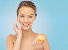 Mujer joven feliz que aplica la crema a su cara Imagen de archivo