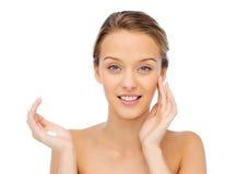 Mujer joven feliz que aplica la crema a su cara Imagen de archivo libre de regalías