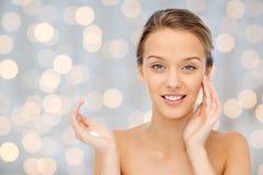 Mujer joven feliz que aplica la crema a su cara Fotos de archivo