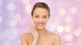 Mujer joven feliz que aplica la crema a su cara Foto de archivo