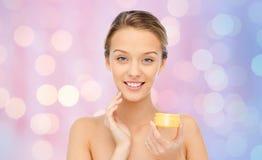 Mujer joven feliz que aplica la crema a su cara Fotografía de archivo