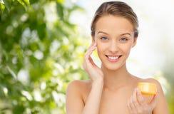 Mujer joven feliz que aplica la crema a su cara Fotografía de archivo libre de regalías
