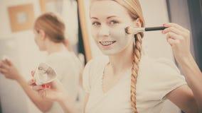 Mujer joven feliz que aplica la máscara del fango en cara Imagen de archivo libre de regalías