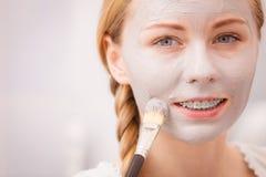 Mujer joven feliz que aplica la máscara del fango en cara Imagen de archivo