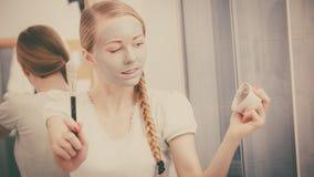 Mujer joven feliz que aplica la máscara del fango en cara Imagenes de archivo