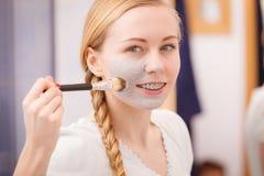 Mujer joven feliz que aplica la máscara del fango en cara Fotografía de archivo