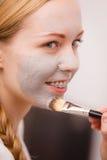 Mujer joven feliz que aplica la máscara del fango en cara foto de archivo
