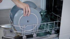 Mujer joven feliz que arregla las placas en el lavaplatos At Home