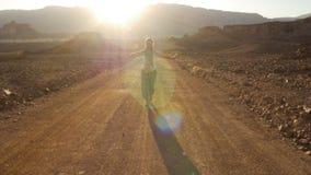 Mujer joven feliz que camina en camino del desierto en puesta del sol con la llamarada hermosa del sol Parque de Timna, Israel metrajes