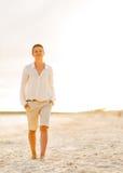 Mujer joven feliz que camina en la playa en la tarde Fotografía de archivo