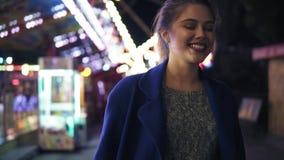 Mujer joven feliz que camina en parque de atracciones, la sonrisa y la risa Diversas atracciones en el fondo A cámara lenta almacen de metraje de vídeo