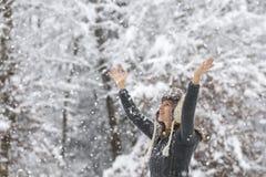 Mujer joven feliz que celebra invierno aumentando sus brazos para arriba en t fotografía de archivo