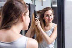 Mujer joven feliz que cepilla el pelo largo delante del espejo Fotografía de archivo libre de regalías