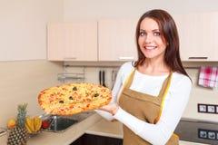 Mujer joven feliz que cocina la pizza Foto de archivo libre de regalías
