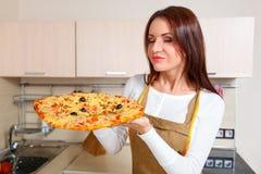 Mujer joven feliz que cocina la pizza Fotos de archivo libres de regalías