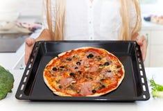 Mujer joven feliz que cocina la pizza en casa Fotos de archivo libres de regalías