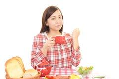 Mujer joven feliz que come comidas imagen de archivo