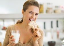 Mujer joven feliz que come el pan quebradizo con leche en cocina Imagen de archivo