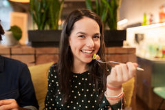Mujer joven feliz que come en el restaurante Fotografía de archivo