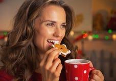 Mujer joven feliz que come la galleta de la Navidad Imagenes de archivo