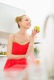 Mujer joven feliz que come la manzana en cocina Fotos de archivo libres de regalías