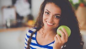 Mujer joven feliz que come manzanas en cocina Fotos de archivo