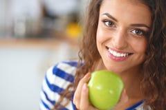 Mujer joven feliz que come manzanas en cocina Foto de archivo libre de regalías