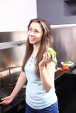 Mujer joven feliz que come manzanas en cocina Foto de archivo