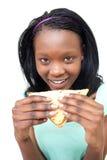 Mujer joven feliz que come un emparedado Foto de archivo libre de regalías