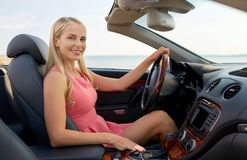 Mujer joven feliz que conduce el coche convertible imagen de archivo libre de regalías