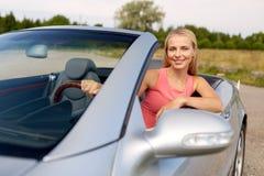 Mujer joven feliz que conduce el coche convertible imagenes de archivo