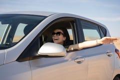 Mujer joven feliz que conduce un coche alquilado en el desierto de Israel imagenes de archivo