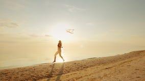 Mujer joven feliz que corre con una cometa almacen de metraje de vídeo