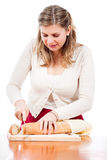 Mujer joven feliz que corta el pan fresco Fotografía de archivo libre de regalías