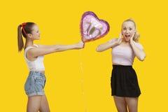 Mujer joven feliz que da el globo del cumpleaños a la mujer sorprendente que se coloca sobre fondo amarillo Fotos de archivo libres de regalías