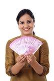 Mujer joven feliz que detiene al indio 2000 notas de la rupia Foto de archivo libre de regalías