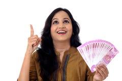 Mujer joven feliz que detiene al indio 2000 notas de la rupia Imagen de archivo