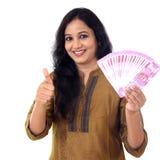 Mujer joven feliz que detiene al indio 2000 notas de la rupia y que hace thu Imagenes de archivo