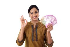 Mujer joven feliz que detiene al indio 2000 notas de la rupia y que lo hace muy bien Foto de archivo