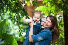 Mujer joven feliz que detiene a un bebé hacia fuera en un paseo en el parque imagenes de archivo