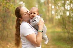 Mujer joven feliz que detiene y que besa a su poco bebé para aventajar fotografía de archivo libre de regalías