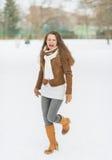 Mujer joven feliz que disfruta de invierno en parque Imagen de archivo libre de regalías