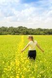 Mujer joven feliz que disfruta de verano y de la naturaleza en el campo de flor amarillo con luz del sol, Harmony And Healthy Lif imagenes de archivo