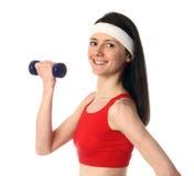 Mujer joven feliz que ejercita con una pesa de gimnasia Foto de archivo