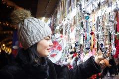 Mujer joven feliz que elige la decoración de la Navidad en el mercado fotografía de archivo libre de regalías
