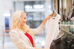 Mujer joven feliz que elige la ropa en alameda Fotografía de archivo